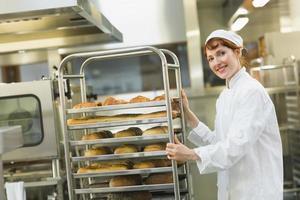 mooie jonge vrouwelijke bakker die een karretje duwt foto