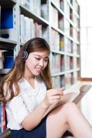 Aziatische mooie vrouwelijke studentenstudie in bibliotheek