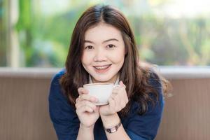gelukkig Aziatische lachende vrouwelijke student koffie drinken