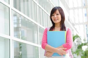 Aziatische Chinese college vrouwelijke student met campus achtergrond foto