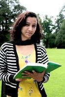 gelukkige Indische vrouwelijke student die zich op gras bevindt. foto