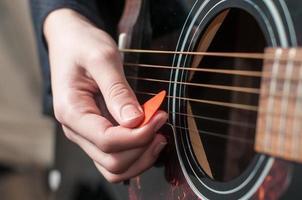 vrouwelijke hand akoestische gitaar spelen