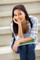 jonge vrouwelijke student buiten zitten foto