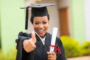 Afrikaanse vrouwelijke afgestudeerde duim opgevend foto