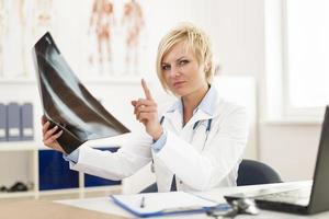vrouwelijke arts die x-ray beeld controleert foto