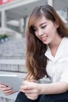 Aziatische vrouwelijke student die tablet in campus gebruiken