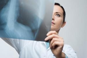 vrouwelijke arts die x-ray beeld onderzoekt foto