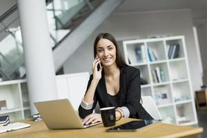 lachende jonge vrouw met laptop en mobiele telefoon in een kantoor foto