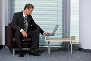 zakenman die laptop in bureau met behulp van foto