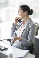 glimlachende jonge onderneemster die op vaste telefoon in bureau spreekt foto