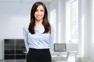 lachende jonge vrouwelijke manager in haar kantoor foto