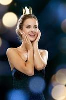 glimlachende vrouw in avondjurk die kroon draagt