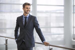 vriendelijke en glimlachende zakenman kijken naar de horizon foto