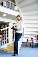 knappe intelligente kerel die een boek in een bibliotheek leest