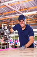 senior textiel fabrieksarbeider snijden stof foto