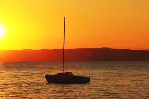 zonsondergang over het meer met schip foto