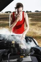 mooie brunette die ongerust de rokende motor van gestrande auto onderzoekt foto