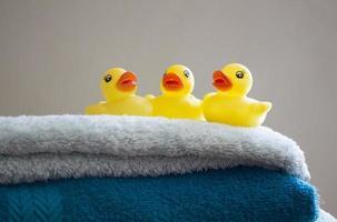 drie gele badeendjes op een stapel gevouwen handdoeken foto