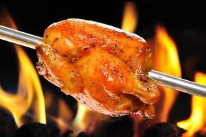 geglazuurde rotisserie kip wordt geroosterd boven een open vuur foto
