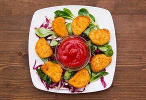 nuggets van kip over salade op hout van boven foto