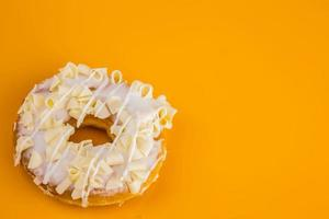 witte chocoladedoughnut op gele achtergrond foto