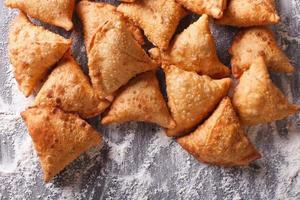 stapel bakken samosa's op bebloemde tafel. horizontaal bovenaanzicht