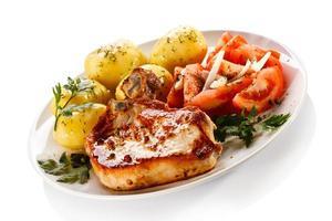 karbonade, gekookte aardappelen en groenten op witte achtergrond foto