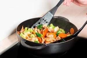 frituren ontmoeten en groenten in koekenpan met handen foto
