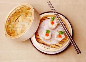 Chinese dumplings met zeevruchten gegarneerd met rode kaviaar en peterselie foto