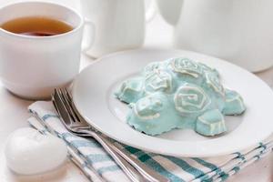 schildpad vormige cake op witte plaat, geruite servet, thee foto