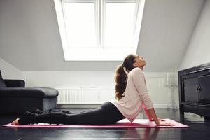 vrouw die zich het uitrekken op mat thuis doet foto