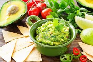 beker met guacamole en maïs chips - traditionele Mexicaanse voorgerecht foto