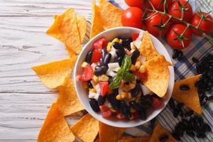 Mexicaanse salsa met bonen en maïschips nacho's. horizontale bovenkant foto
