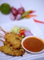 Saté van gegrild varkensvlees met pindasaus en azijn. Thais eten. foto