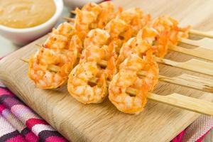 zes stokjes van saté goong op een houten bord op een tafel