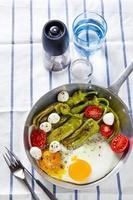 ontbijt in een koekenpan. gebakken eieren met salade.
