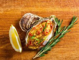 gebakken oesterschelp met kaas, geserveerd greens en citroen foto