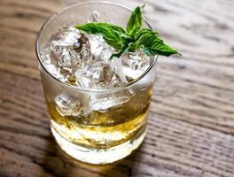 glas rum op de houten achtergrond foto