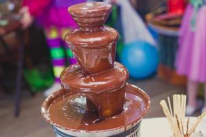 chocoladefontein met fondue, fruit en marshmallow op kinderfeestje foto