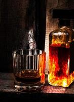 glas whisky whisky en fles op oude houten achtergrond.