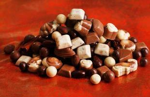 verschillende soorten chocolaatjes op rode achtergrond foto