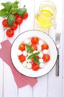 Italiaanse caprese salade witte plaat op een witte achtergrond foto