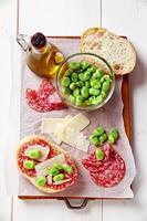 Italiaanse snacks. broodje salami met parmezaanse kaas en brede bea foto
