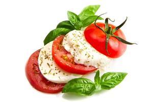 tomaat en mozzarella met basilicumbladeren op wit