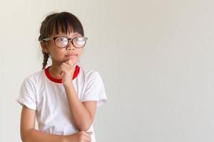Aziatisch meisje kind denkt voor iets foto