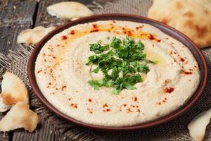 kom hummus, traditionele mediterrane soep met olie, paprika foto