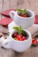 chocolademousse in een witte keramische beker met granaatappel foto