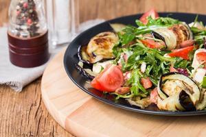 auberginesalade met tomaten en rucola foto