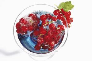 cocktailglas met blauwe curacao en bevroren rode aalbessen foto