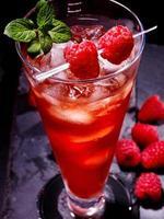 rode cocktail en munt op donkere achtergrond foto